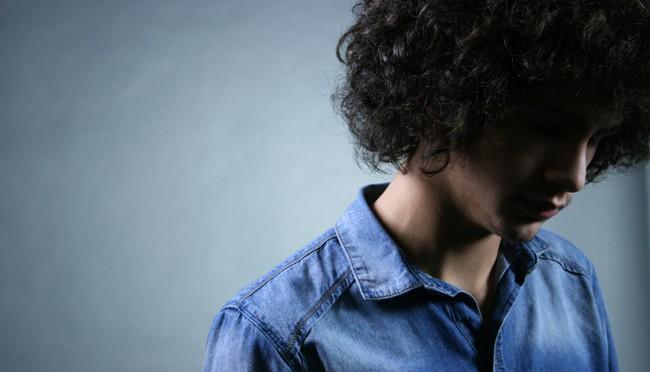 Portraitfoto - Mann mit Locken in blau
